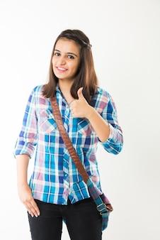 Hübsches indisches oder asiatisches junges college-mädchen, das bücher und tasche hält, während es auf weißem hintergrund steht