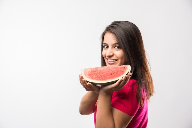 Hübsches indisches oder asiatisches mädchen, das eine scheibe wassermelone oder tarbuja in hindi hält und lokalisiert über weißem oder gelbem hintergrund steht.