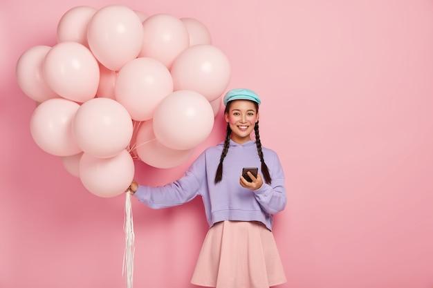 Hübsches japanisches mädchen erhält textnachrichten auf dem handy, chattet online, trägt stilvolle kleidung, blaue mütze, steht mit luftballons, ist auf party, lächelt glücklich