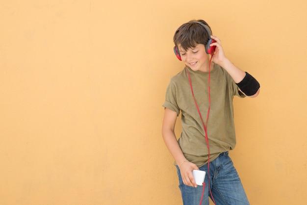 Hübsches jugendlich, ein grünes t-shirt tragend, das musik hört