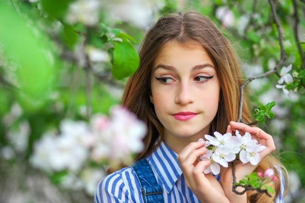 Hübsches jugendlich mädchen, das im garten nahe blütenbaum mit weißen blumen aufwirft. frühlingszeit