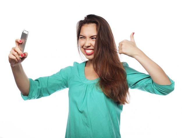 Hübsches jugendlich mädchen, das selfies nimmt