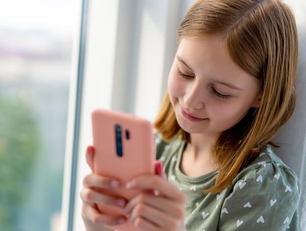 Hübsches jugendliches mädchen, das smartphone anschaut und mit freunden zu hause in der nähe des fensters mit tag chattet ...