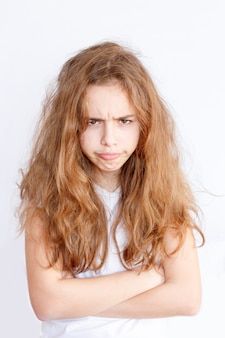 Hübsches jugendlichmädchen mit dem langen haar macht sehr verärgertes lustiges gesicht