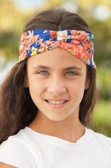 Hübsches jugendlichmädchen mit einem geblühten stirnband