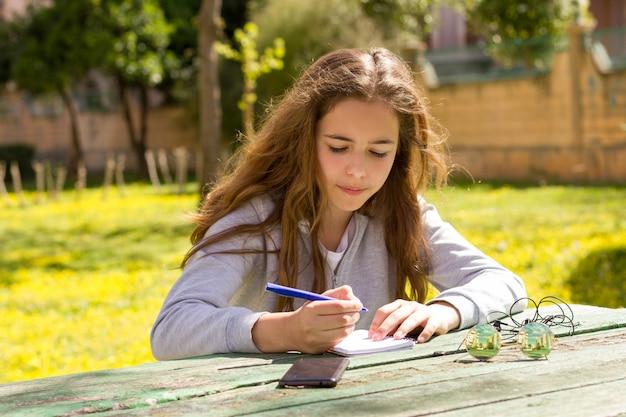 Hübsches jugendlichmädchen mit mobilem cellpfone smartphone am sommerpark