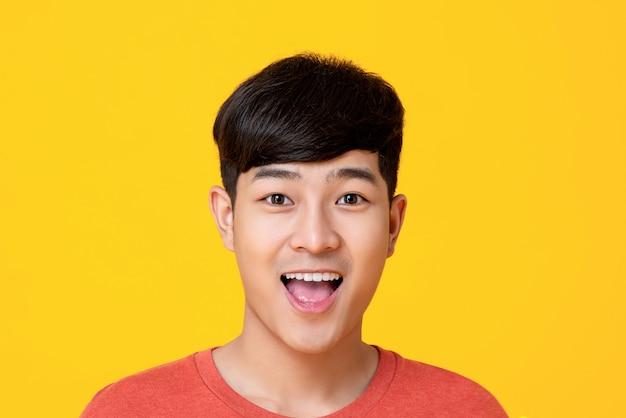 Hübsches junges asiatisches manngesicht, das mit dem mund offen lächelt