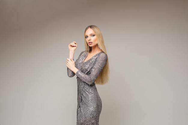 Hübsches junges blondes langhaariges mädchen im glänzenden silbernen kleid, das auf grauem studio aufwirft