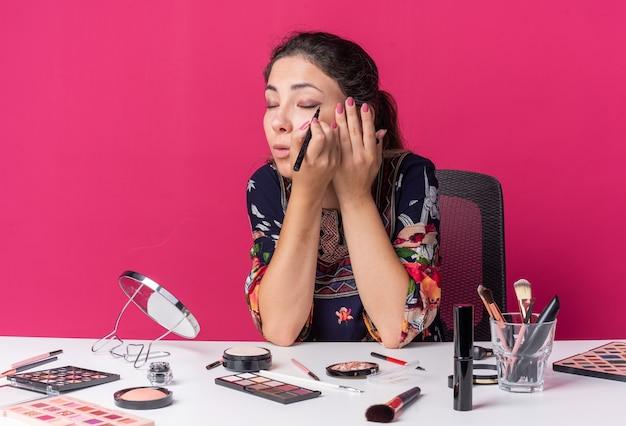 Hübsches junges brünettes mädchen, das am tisch mit make-up-tools sitzt, die eyeliner auftragen