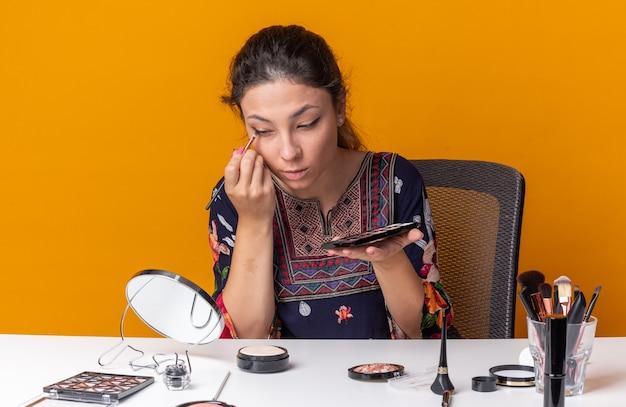 Hübsches junges brünettes mädchen, das am tisch mit make-up-tools sitzt, die lidschatten-palette hält und lidschatten mit make-up-pinsel auf den spiegel aufträgt