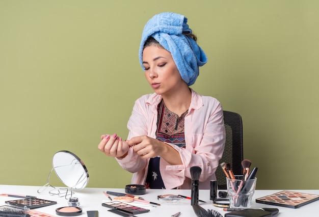 Hübsches junges brünettes mädchen mit eingewickeltem haar im handtuch, das am tisch mit make-up-werkzeugen sitzt, die ihren hemdärmel zuknöpfen