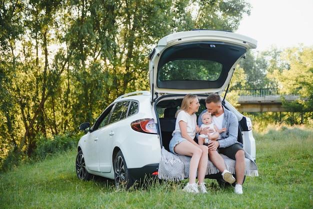 Hübsches junges ehepaar und ihre tochter ruhen in der natur. die frau und das mädchen sitzen auf offenem kofferraum. der mann steht neben ihnen. sie lächeln