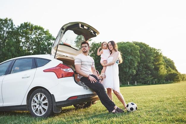 Hübsches junges ehepaar und ihre tochter ruhen in der natur. die mutter, der vater und das kleine mädchen sitzen auf einem offenen kofferraum