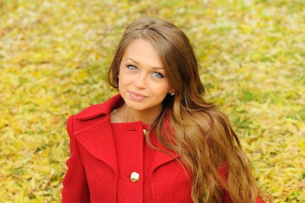 Hübsches junges frauenporträt, das im roten mantel der mode im herbstpark gekleidet wird