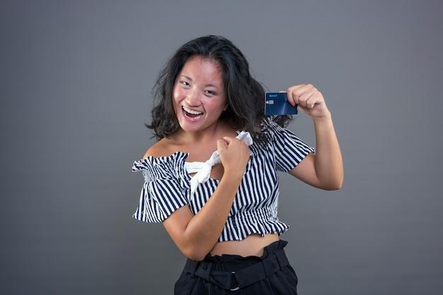 Hübsches junges glückliches und lächelndes chinesisches mädchen, das kreditkarte zeigt