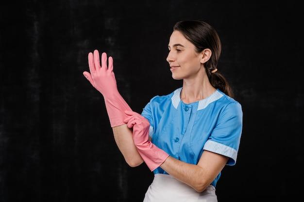 Hübsches junges hotelzimmerservicepersonal in der blauen uniform, die rosa gummihandschuhe vor kamera vor schwarzem hintergrund anzieht