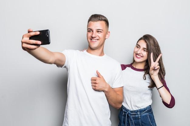 Hübsches junges hübsches paar jungen und mädchen, die selfie auf ihrem telefon lokalisiert auf weiß machen