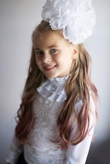 Hübsches junges jugendlich mädchen ist in einer weißen bluse lokalisiert auf grauem hintergrund