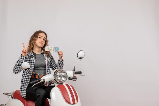 Hübsches junges mädchen auf moped, das ein ticket hält, das ein okey-schild auf grau macht