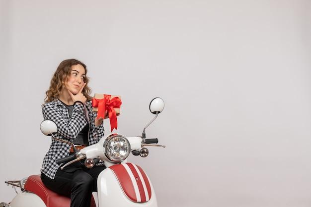 Hübsches junges mädchen auf moped, das geschenk auf grau hält