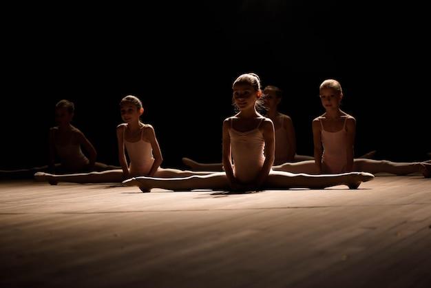Hübsches junges mädchen, das auf der bühne sitzt und sich für balletttänze ausdehnt und trainiert.