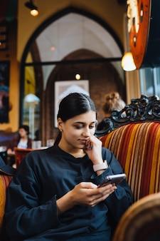 Hübsches junges mädchen, das auf einem großen weichen stuhl in einem café ruht und am telefon plaudert