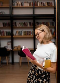 Hübsches junges mädchen, das ein buch an der bibliothek liest