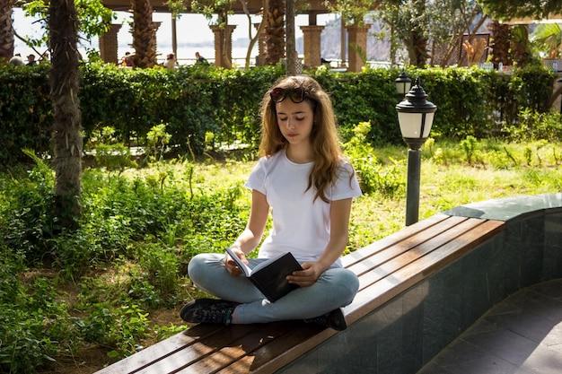 Hübsches junges mädchen, das ein buch auf einer bank in einem park liest