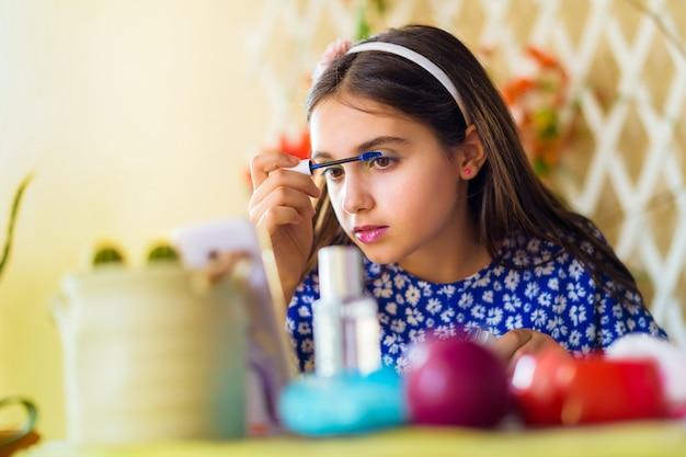 Hübsches junges mädchen, das einen make-up-kurs online verfolgt