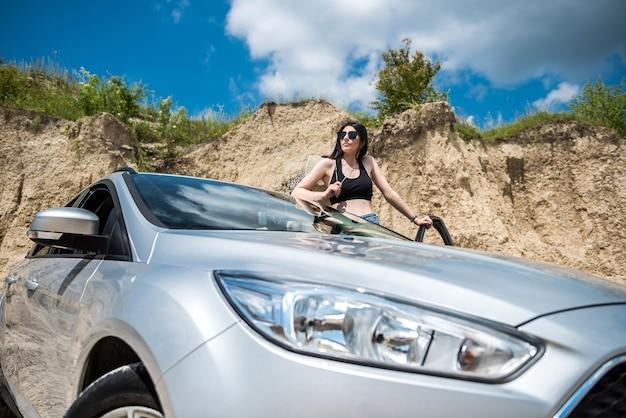 Hübsches junges mädchen, das in den sommerferien nahe dem auto in einem sandsteinbruch aufwirft