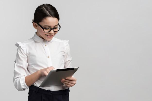 Hübsches junges mädchen, das tablette mit kopienraum hält