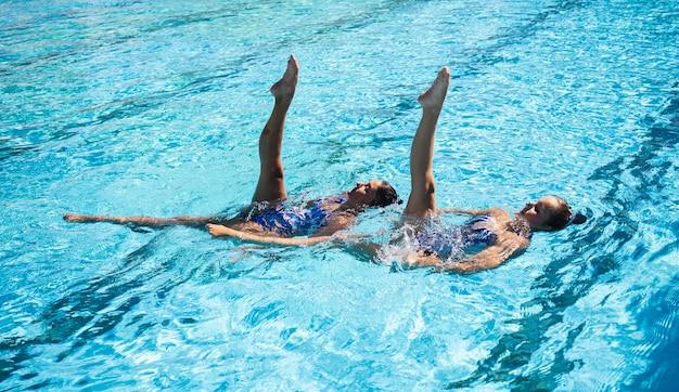 Hübsches junges mädchen, das zusammen schwimmt