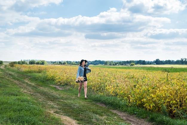 Hübsches junges mädchen genießen sommerferien, die auf ländlichem feld gehen, konzeptglücksgesundheitsfreiheit