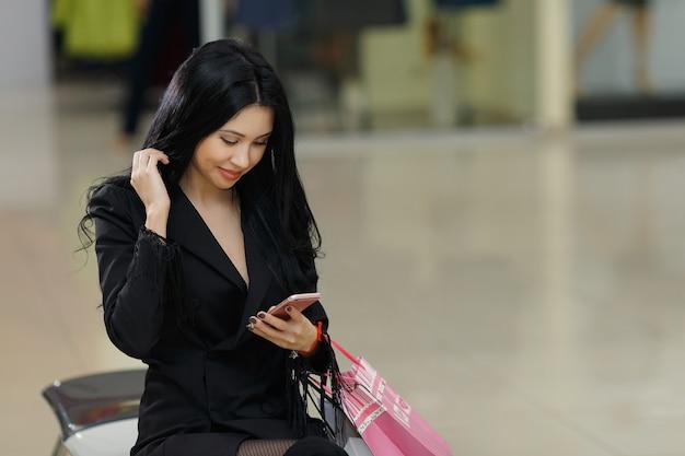 Hübsches junges mädchen hält einkaufstüten und benutzt ein smartphone im einkaufszentrum