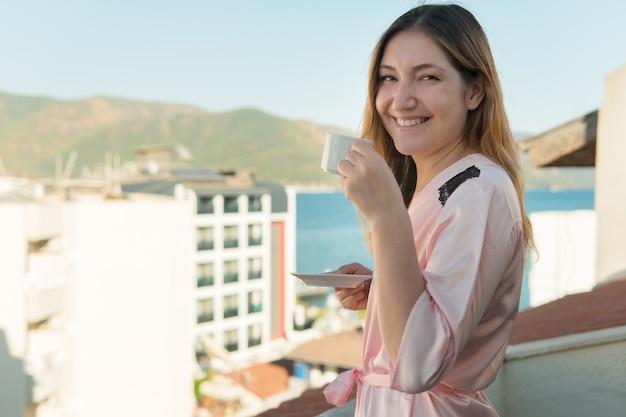 Hübsches junges mädchen im bademantel, das kaffee trinkt, während sie auf dem balkon ihres zimmers im hotel steht und in die kamera schaut