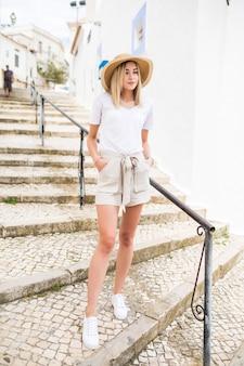 Hübsches junges mädchen im hut geht auf der treppe im freien in der sommerstraße.