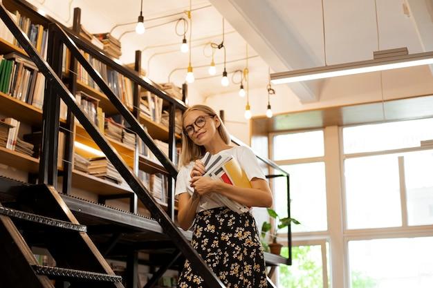 Hübsches junges mädchen in der bibliothek