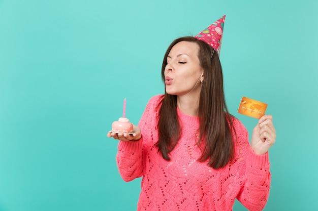 Hübsches junges mädchen in gestricktem rosa pullover, geburtstagshut mit geschlossenen augen, die kerze auf kuchen ausblasen, kreditkarte auf blauem hintergrund in der hand halten. menschen lifestyle-konzept. kopieren sie platz.
