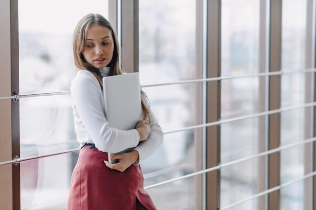 Hübsches junges mädchen mit einem laptop am fenster