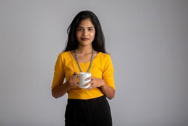 Hübsches junges mädchen mit einer tasse tee oder kaffee, die auf grauer wand aufwirft