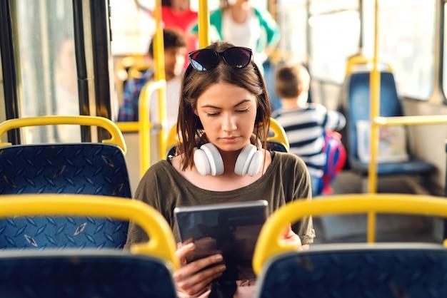 Hübsches junges mädchen mit kopfhörern, die in einem bus sitzen und tablette beobachten.