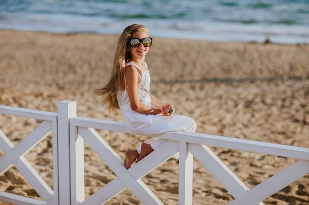 Hübsches junges mädchen mit langen blonden haaren im weißen sommeroverall und in der sonnenbrille, die auf weißem hotelzaun sitzen, der die muschel hält. speicherplatz kopieren.