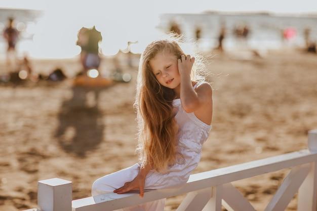 Hübsches junges mädchen mit langen blonden haaren in weißen sommeroveralls, die auf weißem hotelzaun sitzen und die muschel halten. speicherplatz kopieren.