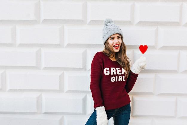 Hübsches junges mädchen mit langen haaren im marsala-pullover mit rotem herzlutscher auf grauer wand. sie trägt weiße warme handschuhe und lächelt.