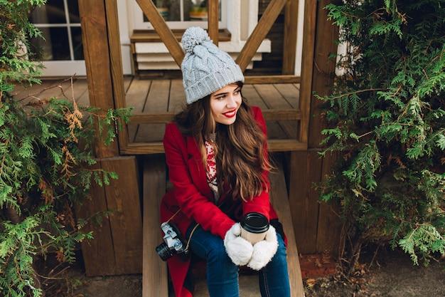 Hübsches junges mädchen mit langen haaren im roten mantel, der auf holztreppen zwischen grünen zweigen im freien sitzt. sie hat eine graue strickmütze, hält kaffee in weißen handschuhen und lächelt zur seite.
