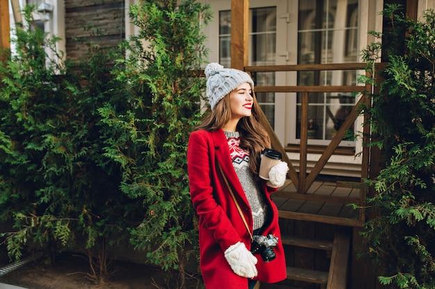 Hübsches junges mädchen mit langen haaren im roten mantel und in der strickmütze, die auf straße auf holzhaus gehen. sie hat eine kamera, hält kaffee in weißen handschuhen.