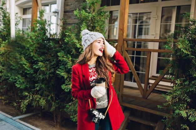 Hübsches junges mädchen mit langen haaren im roten mantel und strickmütze auf holzhaus. sie hält kaffee in weißen handschuhen und drückt sich zur seite.