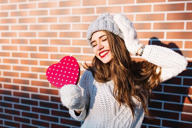 Hübsches junges mädchen mit langen haaren im warmen pullover und strickmütze an der wand draußen. sie hält ein rotes herz in handschuhen und sieht mit geschlossenen augen zufrieden aus.