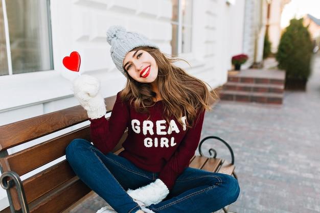 Hübsches junges mädchen mit langen haaren in strickmütze und handschuhen, die auf bank in der stadt sitzen. sie hält ein karamellherz und lächelt.