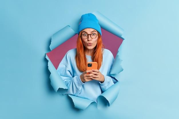 Hübsches junges mädchen mit roten haaren liest beitrag in sozialen netzwerken chats online verwendet handy hält atem sieht verwundert verwendet verwendet moderne gadget in stilvolle kleidung bricht durch papierwand